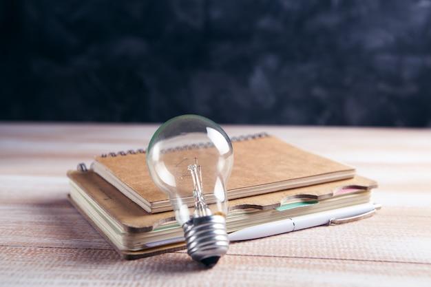 テーブルの上のメモ帳と電球。コンセプトライティングのアイデア