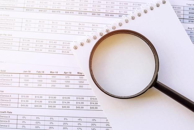Блокнот и увеличительное стекло, лежат на финансовых отчетах