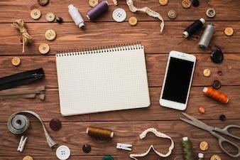 メモ帳と携帯電話は、木製の背景に縫製アクセサリーに囲まれて