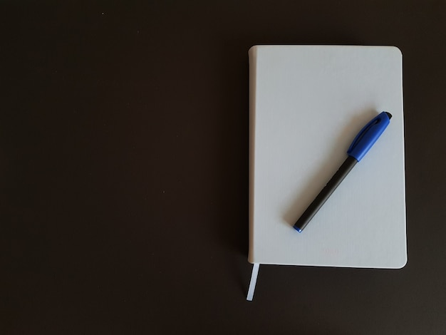 黒の孤立した背景にメモ帳とペン