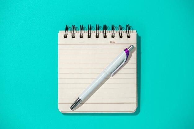 Блокнот и ручка на синем, вид сверху