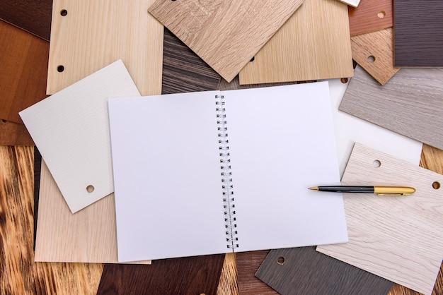 テーブルの上の木製の見本とメモ帳とペン