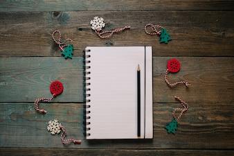 メモ帳と鉛筆、木製クリスマスデコレーション、新年、暗い木製の平らな寝かせフレーム