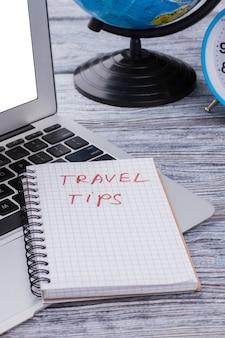 メモ帳と旅行のヒントの概念。木製のテーブルに地球儀を備えたラップトップ。