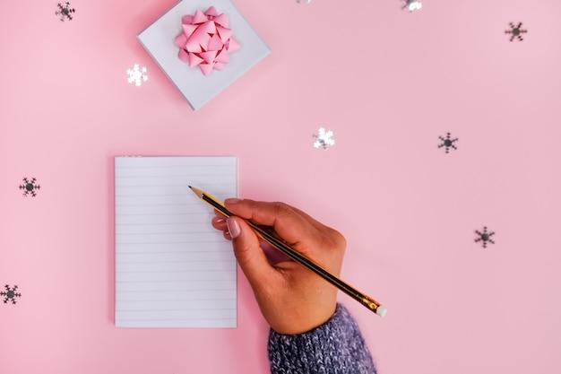 メモ帳とペンで女性の手。