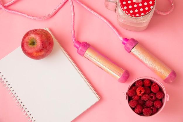 Блокнот яблочный коктейль на розовом фоне с пространством для текста. понятие о спорте, диете, фитнесе, здоровом питании.