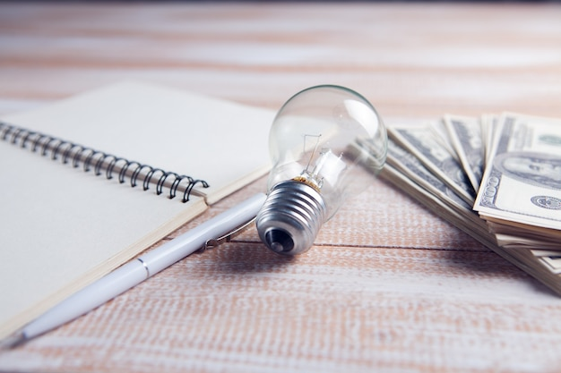 Notepad, banknotes and light bulb