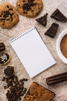 Notepad between coffee beans, biscuits and chocolates
