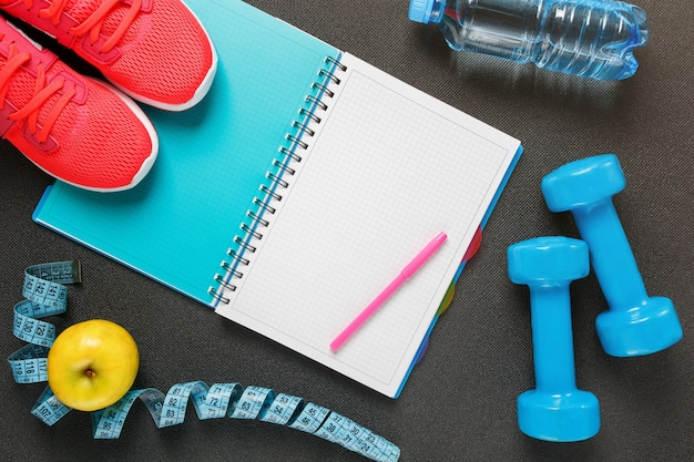 Notepad, a bottle of water, an apple, a skipping rope, dumbbells. healthy diet, lifestyle, concept of dumbbells, exercise