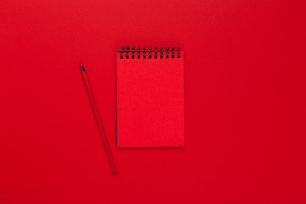 Notepad on a bright colored background, top view