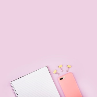 Notepad; bulldog clips and cellphone on pink surface