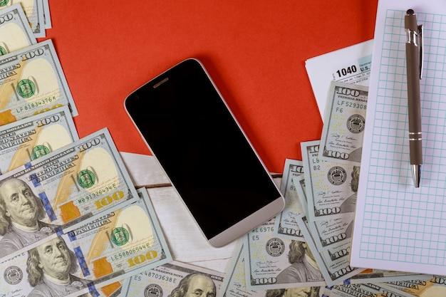 Notepad, cellphone, pen and us dollar bills