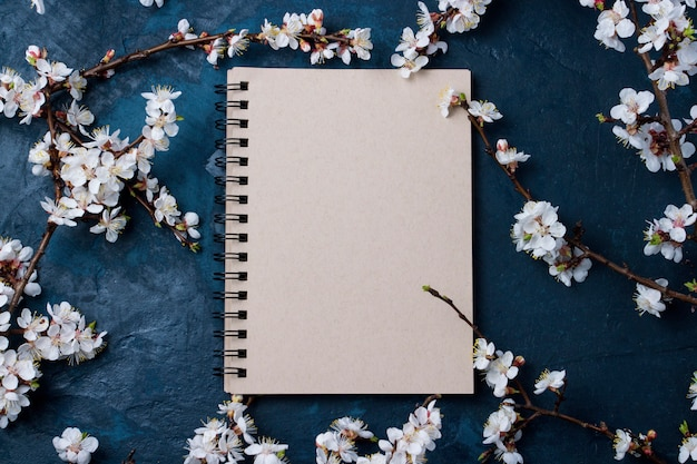 Notepad and cherry branches with spring flowers on a dark blue background