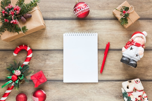Notepad between christmas toys and gift boxes