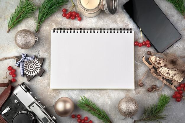 メモ帳、クリスマスのおもちゃ、レトロなカメラ、灰色の表面に赤いガマズミ属の木