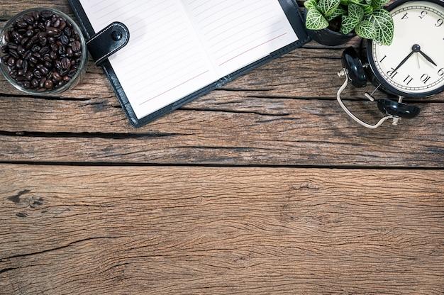 Блокнот, часы, кофейные зерна, помещенные на вид сверху деревянного стола