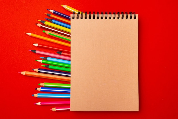 Notepad and color pencils, stationery on working space top view