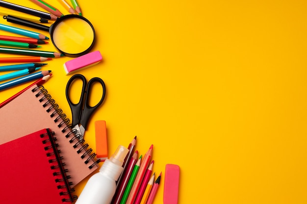 Notepad and color pencils, stationery on yellow