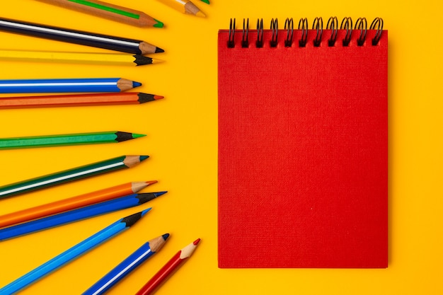 Notepad and color pencils on yellow background