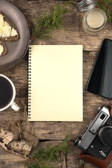 メモ帳、針葉樹の枝、コーヒー、電話、レトロなカメラ