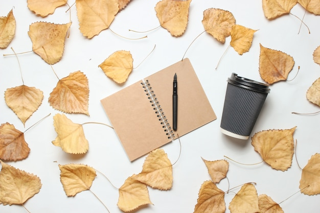 Notepad and cup of coffee with fallen leaves. the concept of journalism, top view.