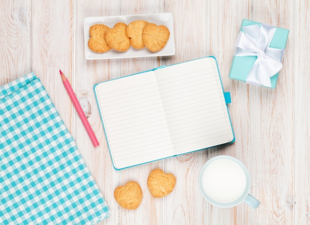 Notepad, cup of milk, heart shaped cookies and gift box on white wooden table