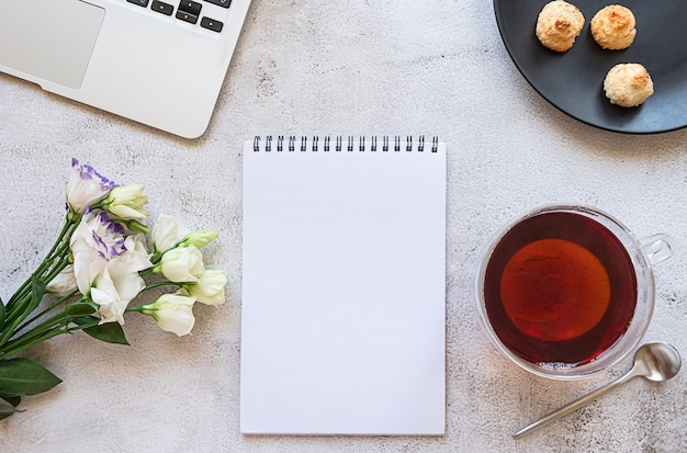 A notepad for daily planning with breakfast setting laptop and flowers