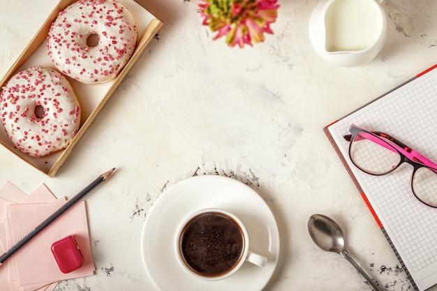 メモ帳、ドーナツ、白いテーブルの上のコーヒー