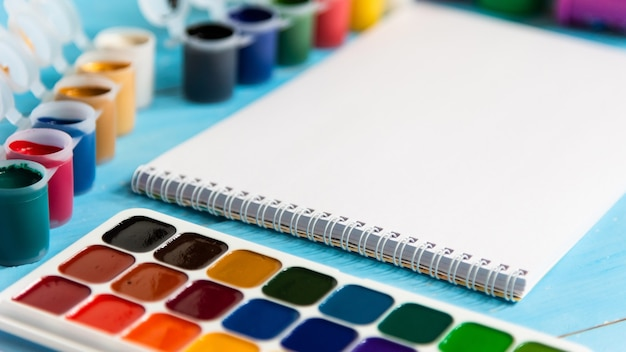 Notepad for drawing with paints and multi-colored paints on a blue background. copy space.