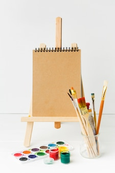 Notepad on easel and paint brushes