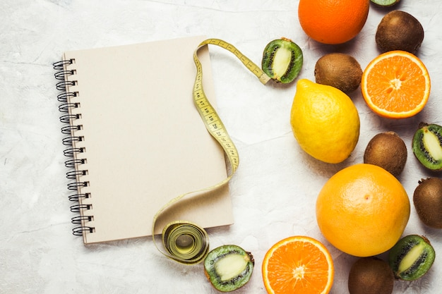 Notepad for entries, measuring tape and organic fruits on a light stone background