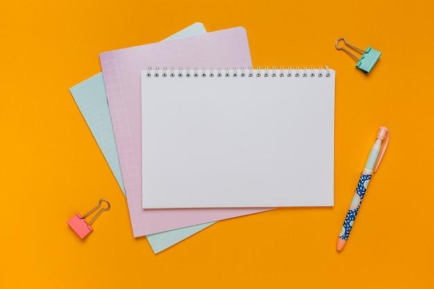メモ帳、練習帳、机の上のペン。オレンジ色の背景のコピースペースオフィスでモックアップ。学校に戻る
