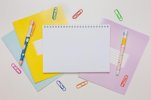 メモ帳、練習帳、机の上のペン。白い背景のコピースペースオフィスでモックアップ。学校に戻る