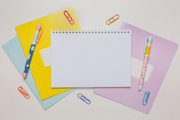 Блокнот, тетрадь и ручка на столе. копируйте в офисе копирования пространство на белом фоне. обратно в школу