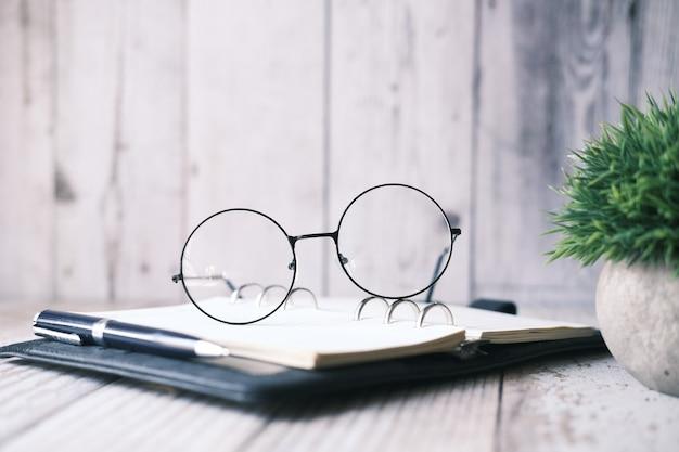 메모장 안경과 나무 테이블에 연필