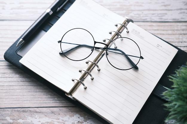 メモ帳、眼鏡、木製のテーブルに鉛筆。