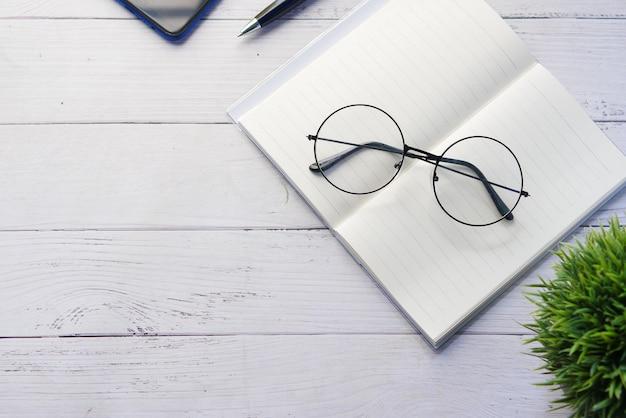 メモ帳の眼鏡と木製のテーブルに鉛筆