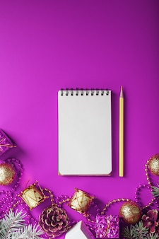 Notepad in festive toys and decorations on a pink purple background.