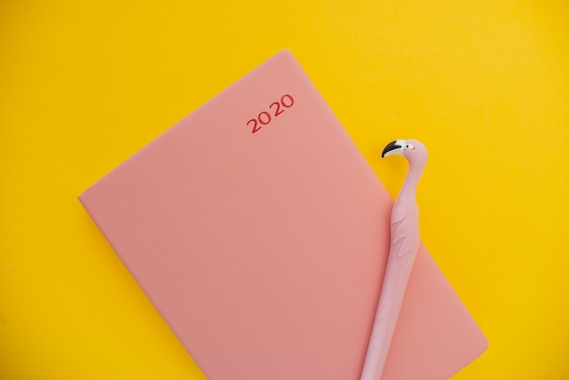 Notepad and flamingo pen  on a yellow abstract background with copy space,
