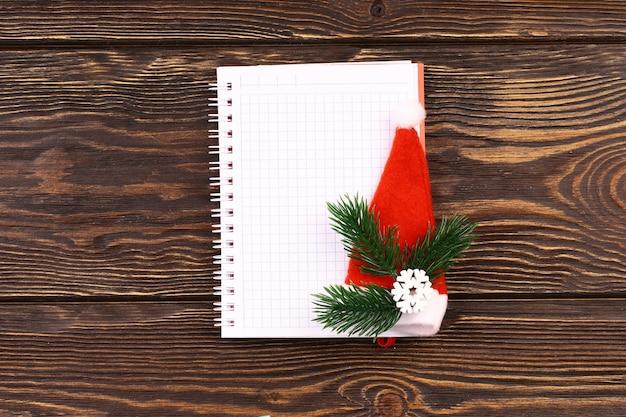 Блокнот для заметок в рождественском стиле на деревянном фоне. записи на новогодний шоппинг. вид сверху, плоский стиль.