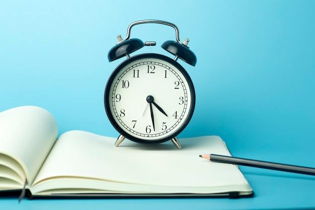 Блокнот для заметок на рабочем столе с будильником. рабочий стол офиса, концепция управления и времени.