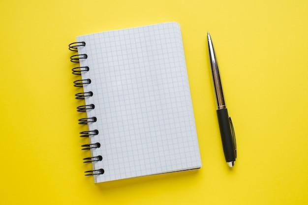 コピースペースを持つ黄色のテーブル上のテキストのメモ帳。教育およびオフィスのコンセプト