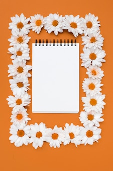 Notepad in frame of daisy flowers