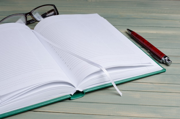 Notepad, glasses, fountain pen on wooden background
