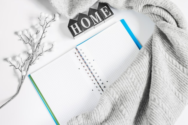 Notepad, gray sweater and a branch on a white background