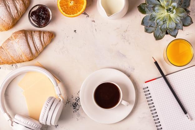 メモ帳、ヘッドフォン、クロワッサン、白いテーブルの上のコーヒー