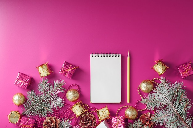 Notepad in holiday toys and decorations on pink christmas background.
