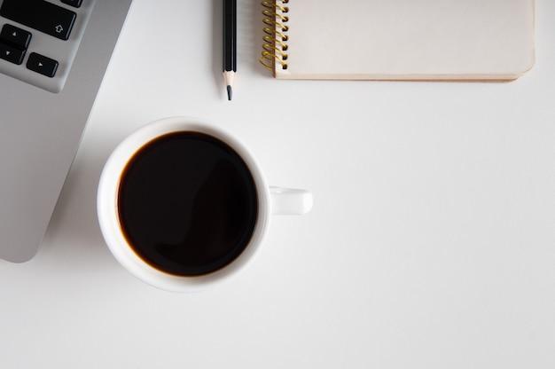 木製のテーブルにメモ帳、ラップトップ、コーヒーカップ