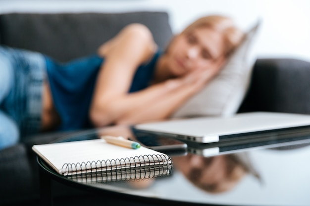 Notepad and laptop on table near woman sleeping on sofa