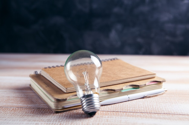 Notepad and light bulb on the table. concept writing ideas